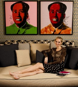 "Lauren Santo Domingo lounges on the couch with her ""Mao"" paintings behind her."