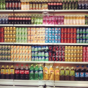 Liu Bolin poses in front of supermarket drinks.