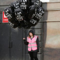 """A disgruntled Dismaland employee holds black balloons that read, """"I am an imbecile."""""""