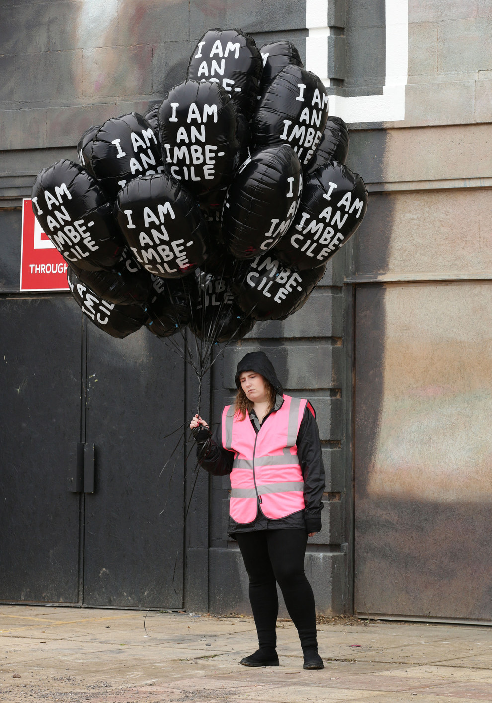 "A disgruntled Dismaland employee holds black balloons that read, ""I am an imbecile."""
