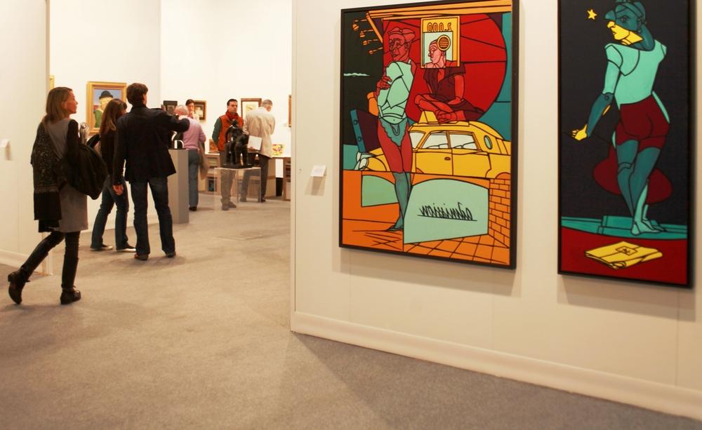People walk in front of art in an art gallery.