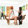 Two women sitting in an art gallery
