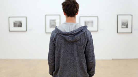 A person in a gray hoodie stands in front of a row of pictures.