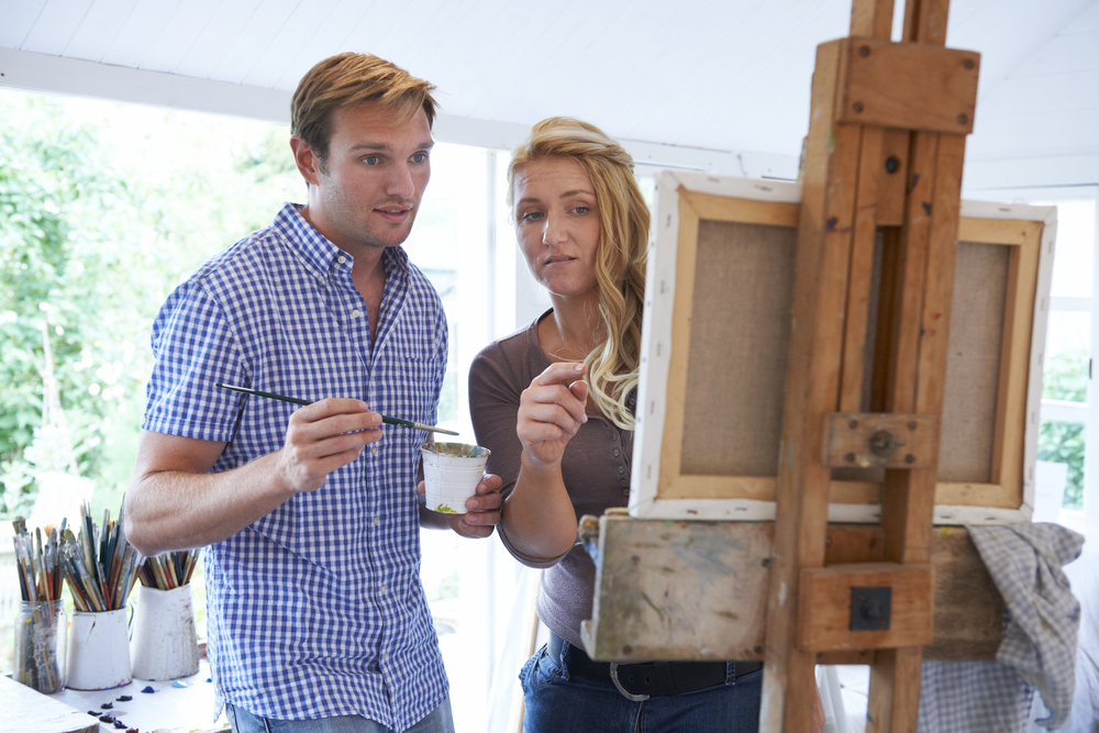 Students work at an easel together.