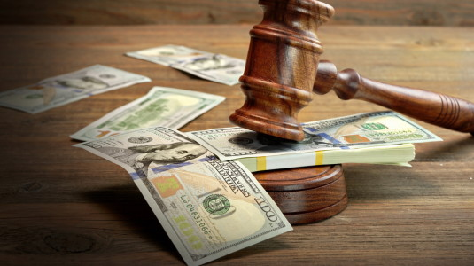 An auction gavel resting on a pile of American currency.
