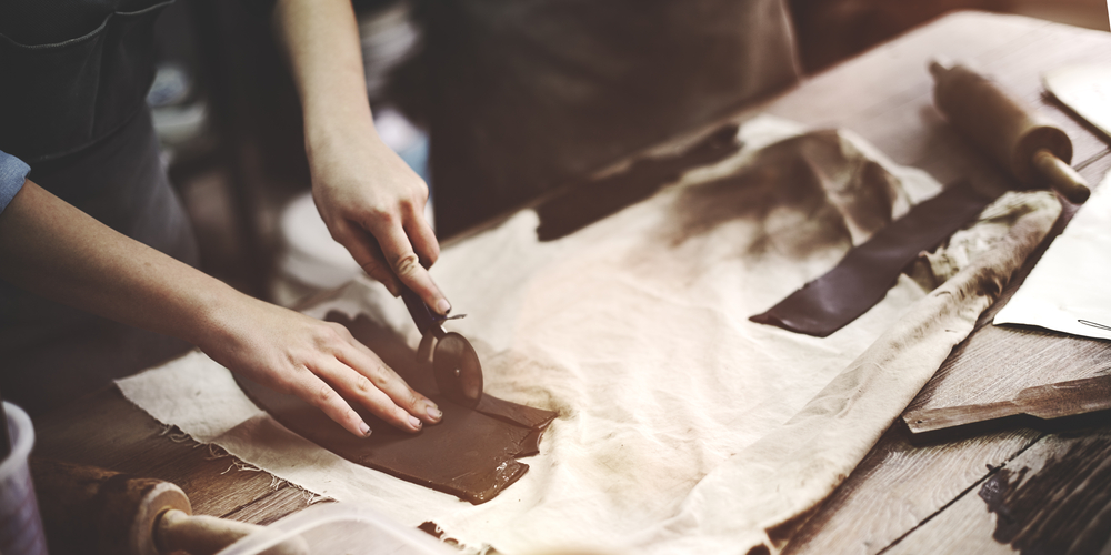 A woman's hands work in a pottery workshop.