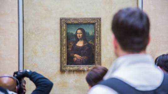 People standing to see the Mona Lisa painting.