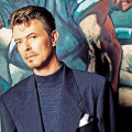 David Bowie stands in front of a painting.
