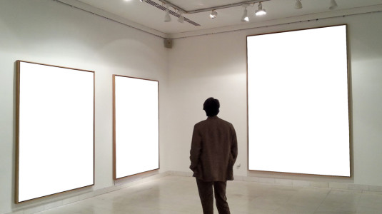 A man's silhouette looks at a series of blank canvases.