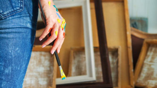 A closeup of a female hand holding a paintbrush.