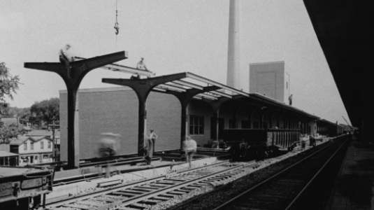 A black and white photo of a rail platform.