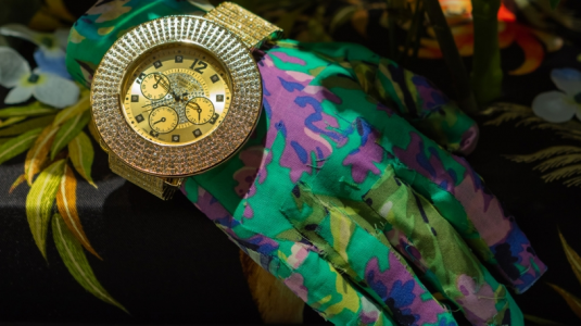 A hand in a colorful glove is decorated with plants and a golden watch.