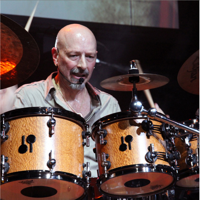Steve Smith plays the drums.