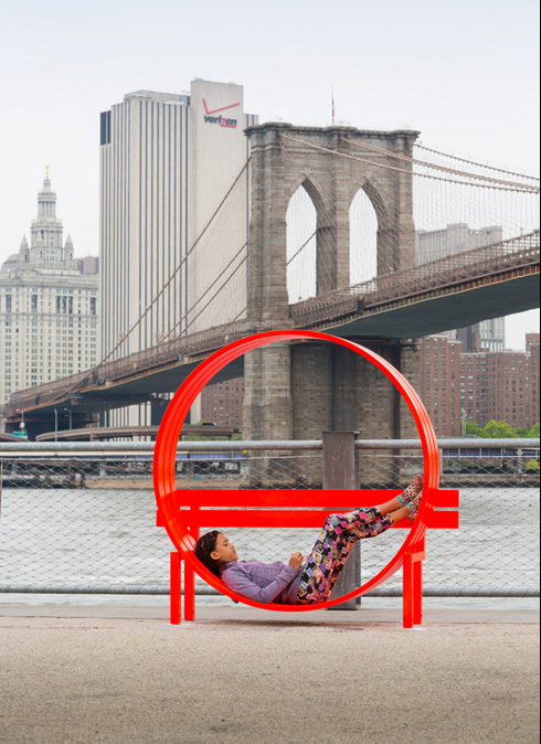 A person rests in an art installation next to the Brooklyn Bridge.