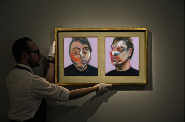 An expert places a Francis Bacon self-portrait up on a wall.