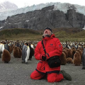 Alexander Ponomarev sits in front of a group of penguins in Antarctica.