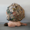 An art piece by Mary Mattingly in which a trash boulder sits on top of a naked woman.