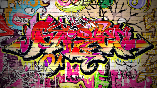 A photograph of vibrant, colorful graffiti covering a brick wall.