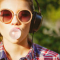 Young girl listening to music with headphones, blowing a bubble with bubblegum