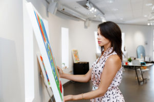 A photograph of a woman taking down a painting in an art gallery.