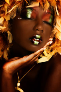A photo of a beautiful African American woman with blonde hair and vivid makeup.