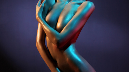 A photo of a naked woman covering her breasts and vagina with her hands.