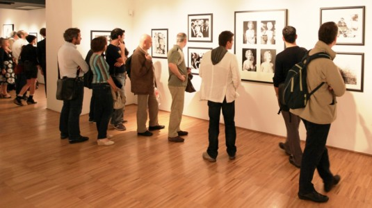 A photo of a crowded art exhibition.