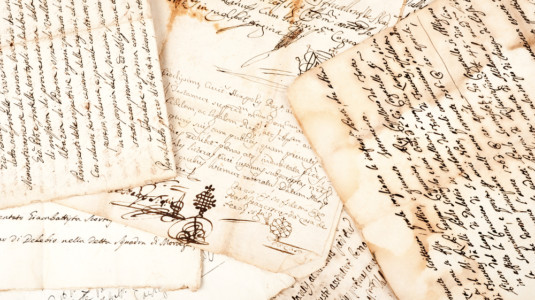 A photo of multiple historic documents (written in calligraphy) scattered about.