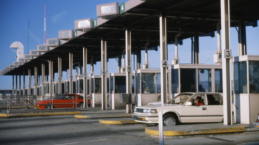 A photo of cars passing through a toll booth.