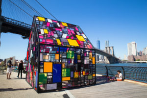 A photo of a stained glass house beneath a New York bridge.