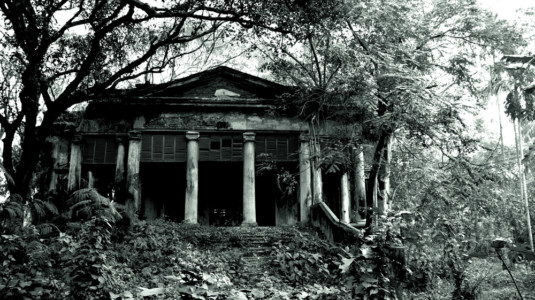 A photo of a creepy looking haunted house, shown in black and white.