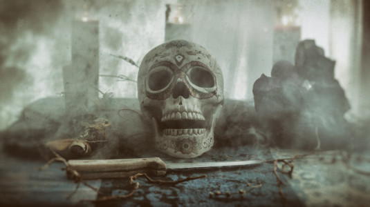 A photo of a skull with a knife in front of it.