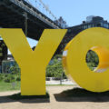 """A photo of a giant yellow sculpture that reads, """"YO."""" The sculpture was created by eminent artist Deborah Kass."""