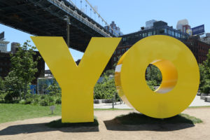 "A photo of a giant yellow sculpture that reads, ""YO."" The sculpture was created by eminent artist Deborah Kass."