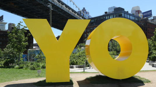 A photo of a giant yellow sculpture that reads,