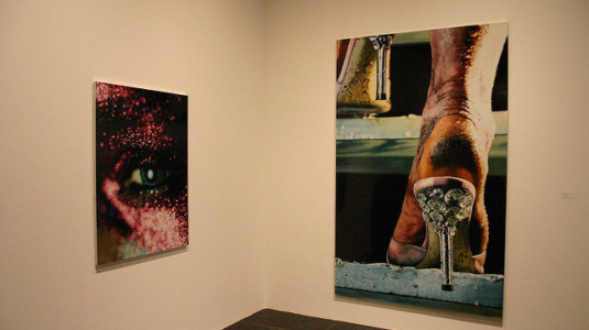 Two photographs by Marilyn Minter on display at an art exhibition.