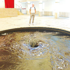 "A photo of Anish Kapoor's ""Descension."" It is a jet black whirlpool in the middle of the ground."