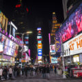 A photo of Times Square taken at night. There are advertisements everywhere.