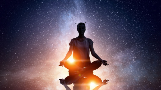 An image of a human figure meditating in cosmic space.