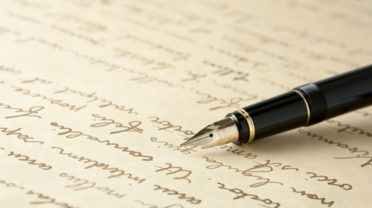 A photo of a handwritten letter with a calligraphy pen on top.