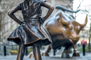 A photo of the Fearless Girl statue and the bronze bull statue.