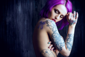 An attractive woman with bright pink hair. She is covered in tattoos.