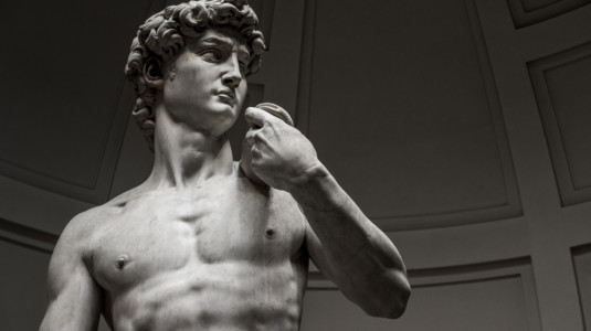 A sculpture of a very fit man. The sculpture is called