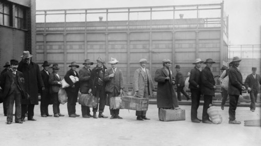 A black-and-white historical photo of Italian men awaiting admission processing at Ellis island. Ca. 1910.