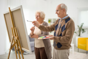 Two elderly artists painting.