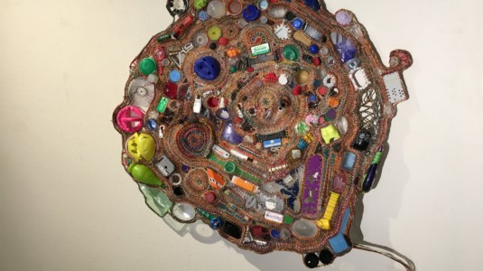 An artwork made from recycled materials. The piece is titled,