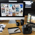 A desktop computer, a laptop, a camera, and some printed pictures on a desk.