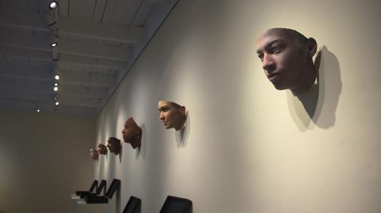 An assortment of masks hung up on the wall inside an art gallery. The masks are part of an exhibition called