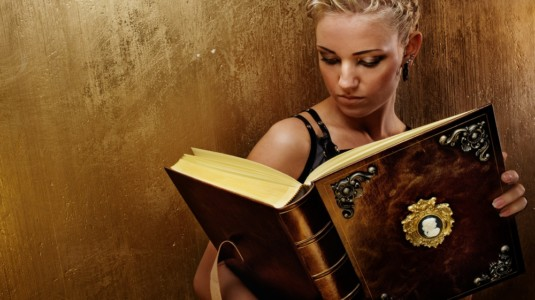 An attractive blonde woman holding a huge, fairy-tale-like book.
