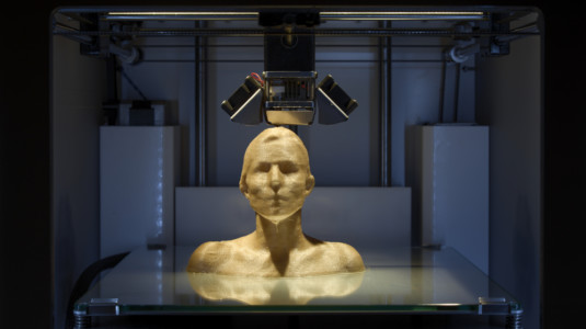A 3D printer manufacturing a golden female sculpture.